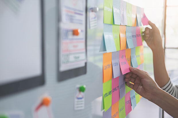 A whiteboard full of colourful post-it notes with hands placing new notes onto the surface